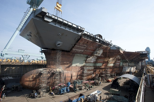 The flight deck of the nuclear-powered aircraft carrier Pre-Commissioning Unit (PCU) Gerald R. Ford (CVN 78) is completed with the addition of the upper bow. The bow weighs 787 metric tons and brings Gerald R. Ford to 96 percent structural completion. (U.S. Navy photo courtesy of Huntington Ingalls Industries, Inc./Released)