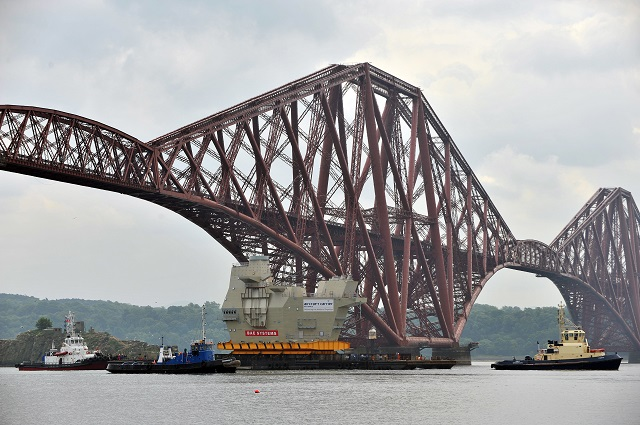 THE HUGE aft island of HMS Queen Elizabeth passed under the Forth Bridge today (Friday June 21) as it made its way to Rosyth, where the ship is being assembled. The iconic section, known as Upper Block 14, was constructed in 90 weeks by Aircraft Carrier Alliance workers at BAE Systems in Scotstoun. The aft island houses HMS Queen Elizabeth's air traffic control systems and will be the centre of all on-board flight operations.