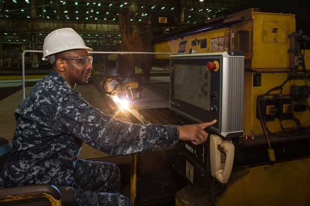 Cmdr. Dave Murray, production officer for the U.S. Navy's DDG 51 program, presses the button to start fabrication of the Ingalls-built destroyer Frank E. Petersen Jr. (DDG 121). Photo by Lance Davis/HII